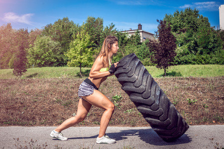Young adult woman flipping and rolling tire during crossfit exercise outdoor. Standard-Bild