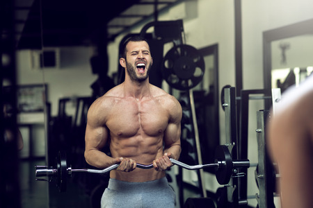 muscle guy: Young adult bodybuilder doing weight lifting in gym while screaming