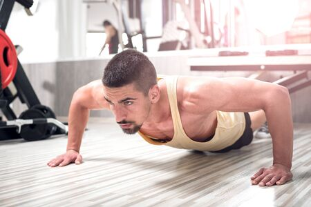 ups: Young adult man doing push ups in gym