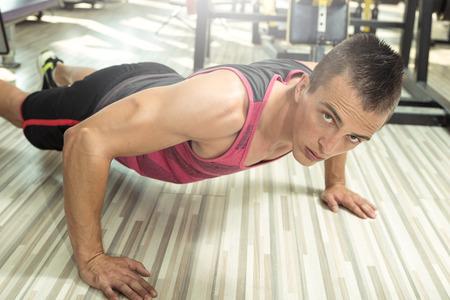 hombres haciendo ejercicio: Hombre adulto joven haciendo flexiones en el gimnasio