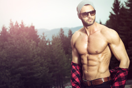 flat stomach: hombre del ajuste hermoso que presenta al aire libre en el bosque que desgasta la camisa marcada