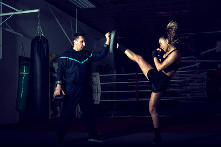 dojo: Young adult sexy woman doing back leg high kick during kickboxing exercise with trainer Stock Photo