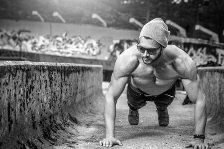 Elegante delgado hombre adulto joven en forma haciendo ejercicio empuje hacia arriba al aire libre en el parque