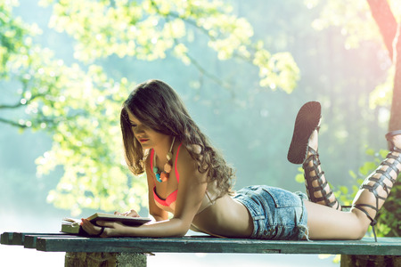 girl lying down: Teenage girl lying down on bench in nature and reading a book.