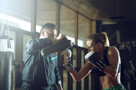 Young adult woman doing kickboxing training with her coach. Standard-Bild