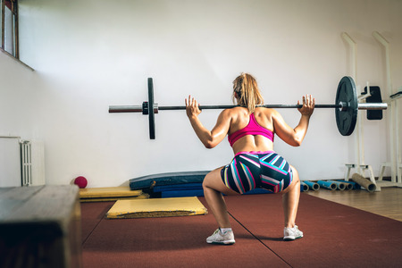 Young adult girl doing heavy duty  squats in gym with barbell. Snatch position. Stock Photo