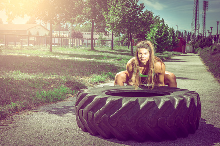 tire: Young adult woman flipping and rolling tire during exercise outdoor. Toned image.