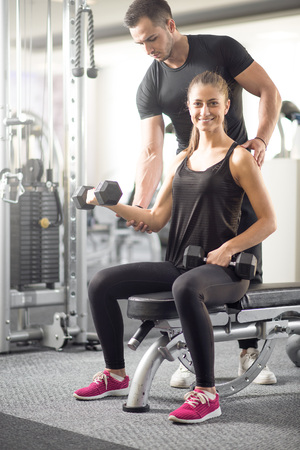 barbel: Young adult woman working out in gym, doing bicep curls with help of her personal trainer. Stock Photo