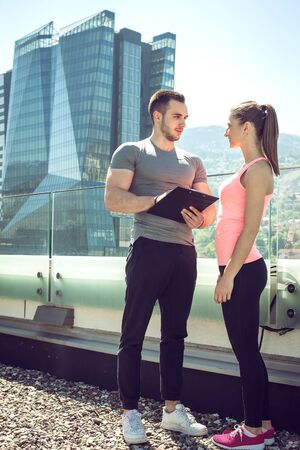 Personal fitness coach showing his female client results outdoors and giving her advices for further achievements.
