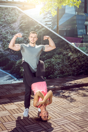 dare: Young attractive couple doing advanced double dare crunches while standing on rooftop of the building in urban area.