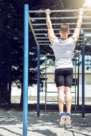 pullups: Muscular man doing pull-ups in outdoor gym park during bright hot summer day. Toned image.