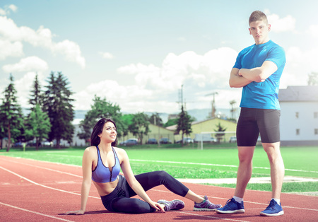 demotivated: Young adult fitness woman posing outdoors at athletic track with her personal trainer.