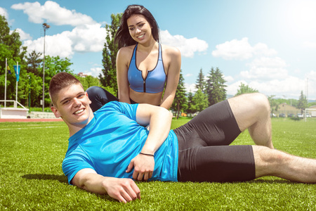 outdoor training: Young adult fitness couple lying on grass outdoor and relaxing after hard training. Toned image.