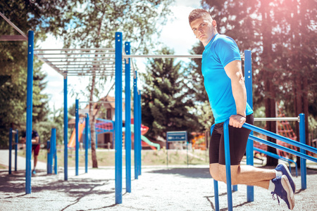 Young fit man doing dips exercise outdoor in open air gym. Toned image.