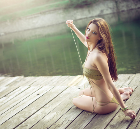 monokini: Attractive young woman posing on pier on mountain lake wearing stylish trendy monokini swimsuit. Toned image. Artistic filters applied. Stock Photo