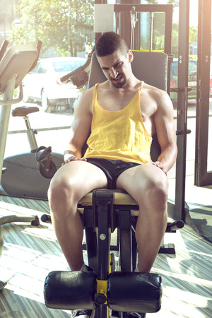 extremity: Young adult man doing leg extension workout exercise in gym Stock Photo