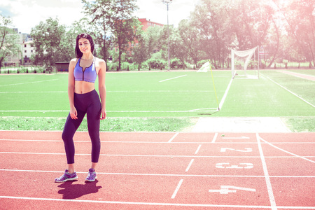 athletics track: Young woman standing on athletics track during hot summer day. Toned image.