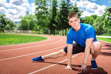 in the open air: Man doing stretching exercises on open air athletics track field during hot summer day. Toned image.