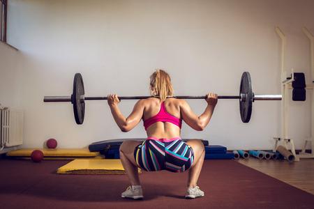 mujeres de espalda: Muchacha adulta joven que hace sentadillas para uso industrial en el gimnasio con mancuerna
