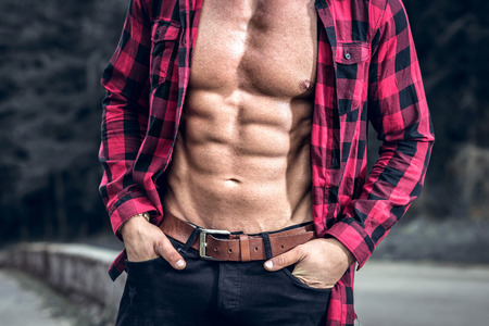 checked shirt: Handsome fit man posing outdoors in forest wearing checked shirt