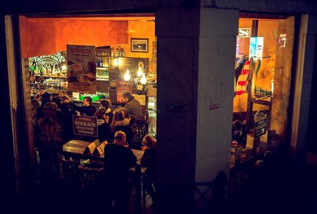 establishment: VENICE, ITALY - MARCH 12, 2016: People having fun in bar in Venice, Italy. Drinking establishment, peek view. Toned image.
