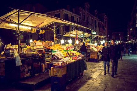 the merchant of venice: VENICE, ITALY - MARCH 12, 2016: Street fruit and vegetables vendor market in Venice, Italy during late night. Tourist passing by. Toned image.