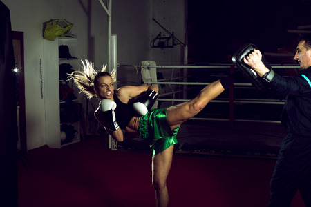Young adult woman doing high kick during kickboxing training exercise Foto de archivo