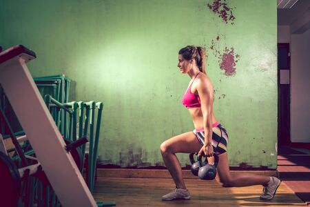lunge: Young adult caucasian girl doing lunge exercise indoor with kettlebell. Toned image.
