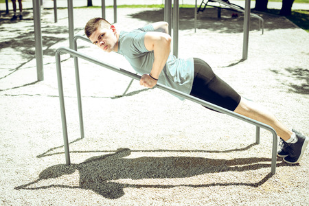 improvisation: Young adult fit bodybuilder doing push-ups exercise in outdoor park gym open air facility. Toned image. Strong will.
