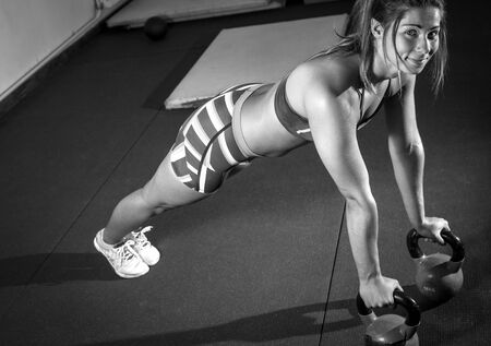 pushup: Fitness woman doing kettlebell pushup exercise at gym