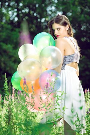 view from behind: Girl posing in nature with balloons. View from behind. Stock Photo