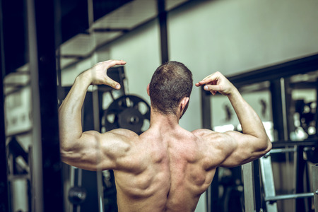 trapezius: Man showing back in gym