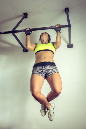 Strong young adult woman doing pull up exercise indoor. Stock Photo