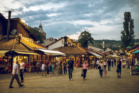 locals: SARAJEVO, BOSNIA AND HERZEGOVINA - JUNE 30, 2016: Locals and tourists walking through Sarajevo old town in summer evening in month of ramadan. Toned image. Editorial