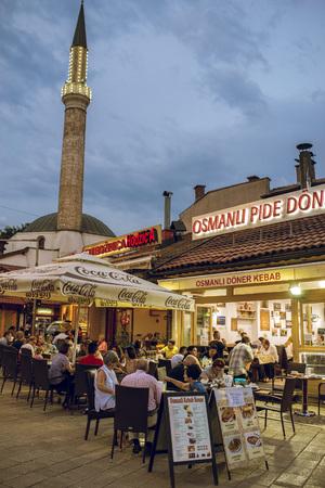 sarajevo: SARAJEVO, BOSNIA AND HERZEGOVINA - JUNE 30, 2016: People having iftar dinner on streets of Sarajevo, Bosnia, during holy muslim month of Ramadan. Toned image.