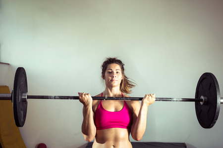 willpower: Young adult girl doing heavy weightlifting during gym active exercise. Strong willpower. Toned image.