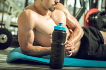 gym floor: Man posing on gym floor with protein shake mix.
