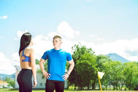 Young adult couple standing and talking on athletics track field during hot sunny summer day. Toned image.