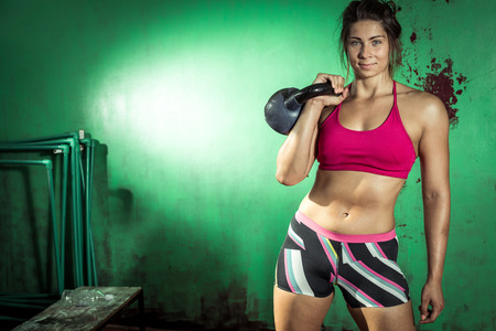 Young adult crossfit girl holding kettlebell Stock Photo
