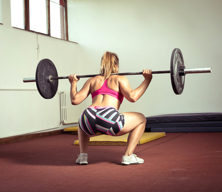 squats: Young adult girl doing heavy duty  squats in gym with barbell