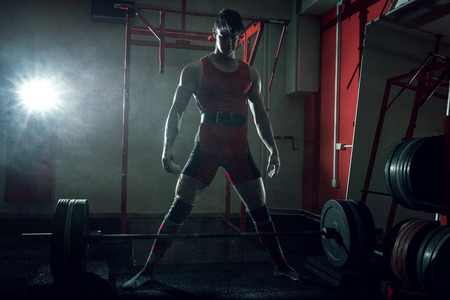 Young adult fit athlete preparing to do sumo deadlift exercise using powder for better hand grip. Stock Photo