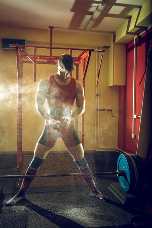 hand grip: Young adult fit athlete preparing to do sumo deadlift exercise using powder for better hand grip. Stock Photo