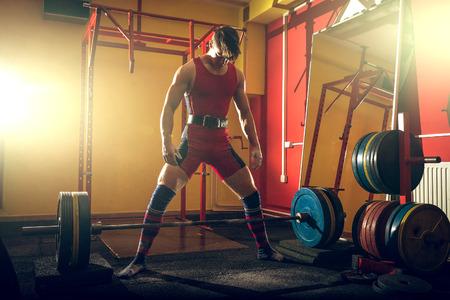 Junge Erwachsene Mann schweren Sumo Kreuzheben Übung im Fitness-Studio-Club. Standard-Bild - 61936317