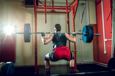 squats: Young teenage man doing squats in indoor gym club.