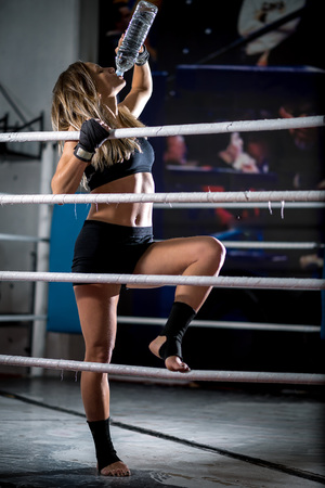 girl punch: Young adult sexy boxing girl drinking water after training