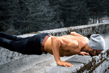 Slim fit elegant young adult man doing push up exercise outdoor in park