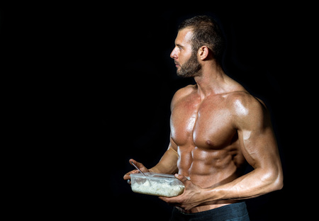 Young adult fit muscular bodybuilder eating healthy white rice from plastic dish isolated.