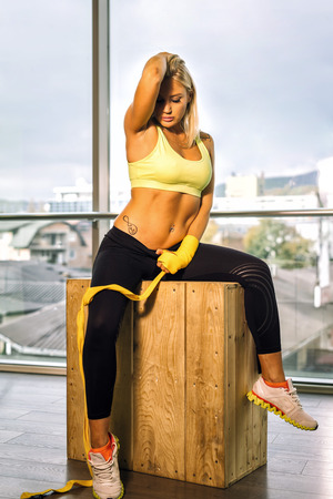 Attractive blond woman sitting on wooden box in fitness center with ties on hands. Toned image.
