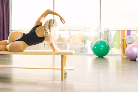 Attractive woman in 30s posing passionate wearing bodysuit on wooden bench in fitness center. Toned image.