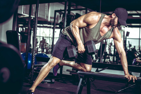 Young handsome adult male doing one-arm dumbbell rows on bench in modern gym